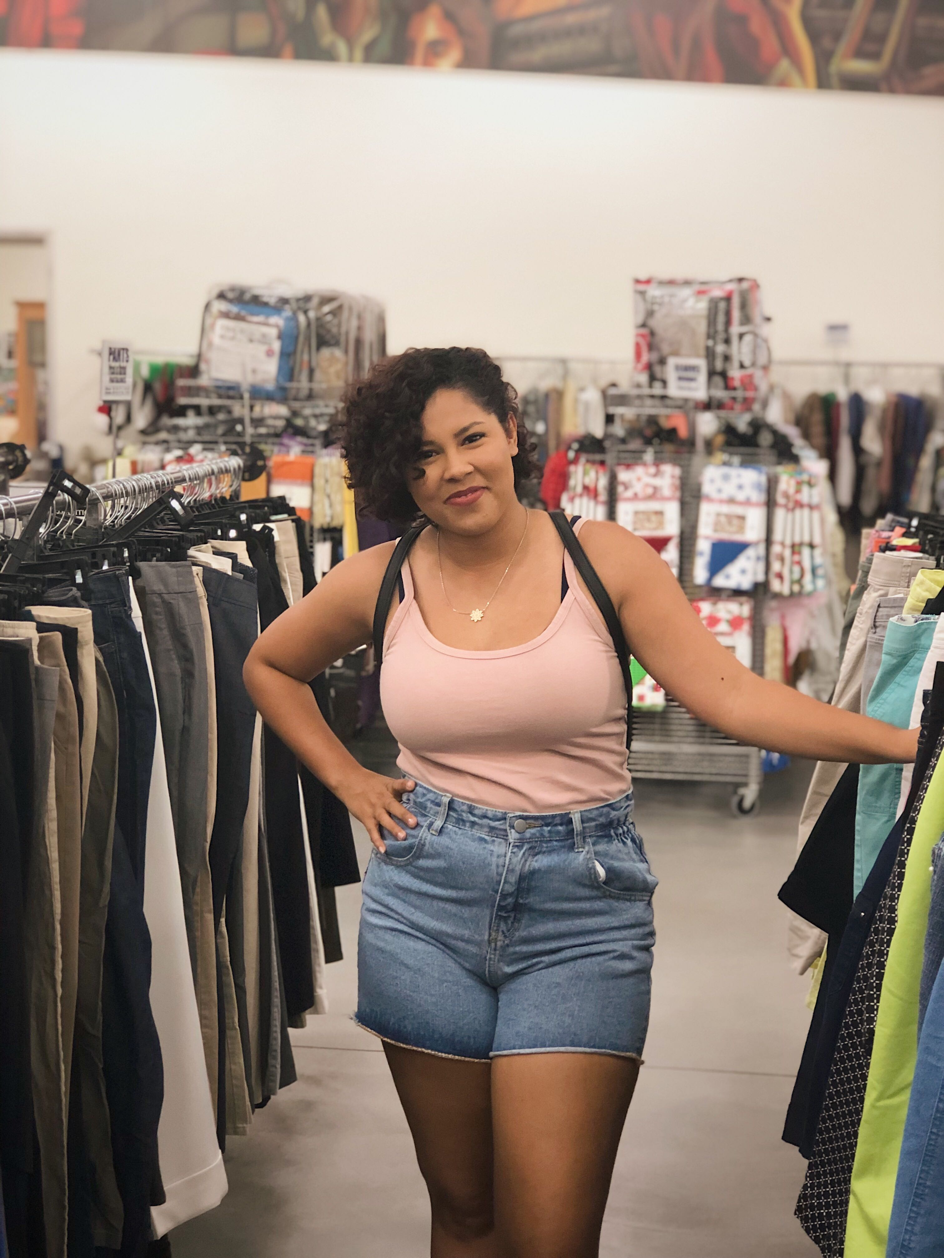 Girl posing between racks in a thrift store smiling in a tan shirt and jean shorts